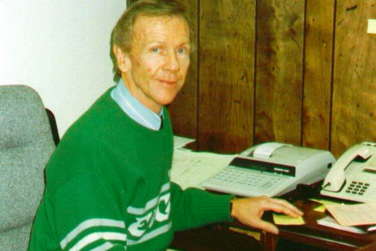 Leo Carlin at his desk in a green Eagles sweater