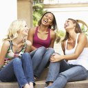 Girlfriends sitting on steps laughing