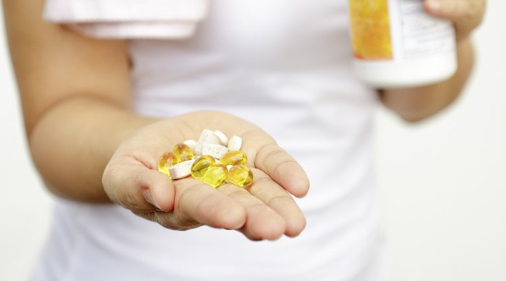 Woman holding vitamins
