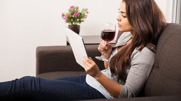 Woman sipping wine on couch