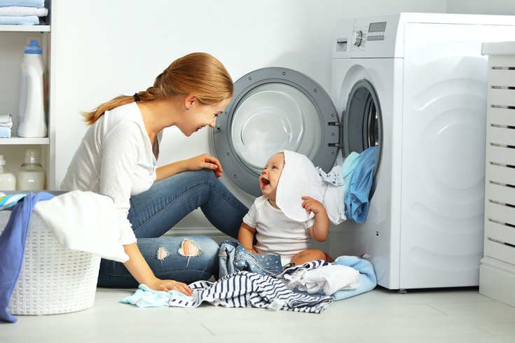 Mother with a baby fold clothes