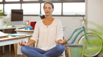 woman meditating in her office